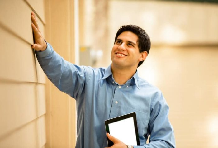 Latin descent building inspector, exterminator, architect, building contractor, engineer, or insurance adjuster examines a building/home's exterior siding wall and window.  He holds a digital tablet.